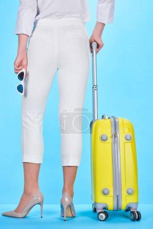 Photo pour Vue arrière de la femme tenant poignée de valise jaune et lunettes de soleil sur fond bleu - image libre de droit