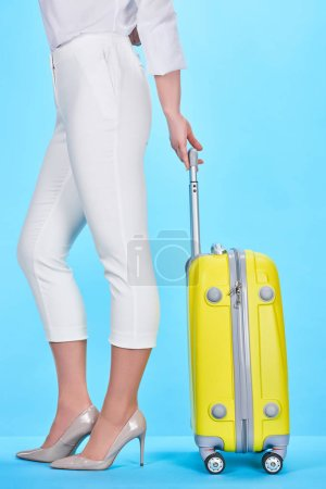 Photo for Side view of woman holding handle of yellow colorful travel bag on blue background - Royalty Free Image