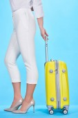 side view of woman holding handle of yellow colorful travel bag on blue background