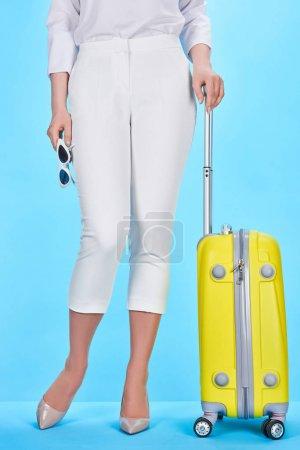 Photo pour Vue recadrée de la femme tenant poignée de sac de voyage coloré jaune et lunettes de soleil sur fond bleu - image libre de droit