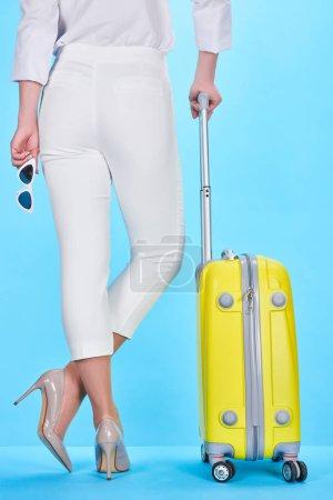 Photo pour Vue arrière de la femme tenant des lunettes de soleil et poignée de sac de voyage coloré jaune sur fond bleu - image libre de droit