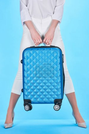 Photo for Partial view of woman posing with blue colorful travel bag on blue background - Royalty Free Image