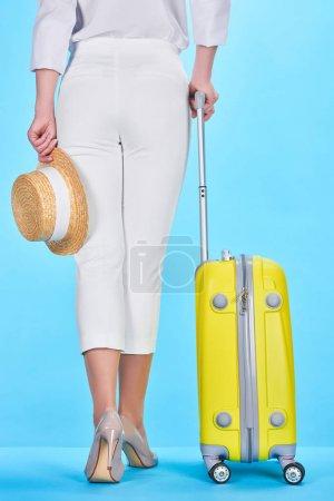 Photo pour Vue arrière de la femme tenant chapeau de paille et poignée de sac de voyage coloré jaune sur fond bleu - image libre de droit