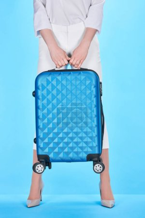 Photo for Cropped view of woman holding blue suitcase on blue background - Royalty Free Image