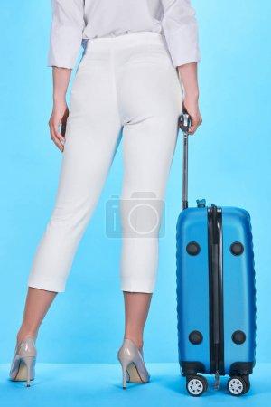 Photo pour Vue arrière de la femme tenant la poignée du sac de voyage bleu sur fond bleu - image libre de droit