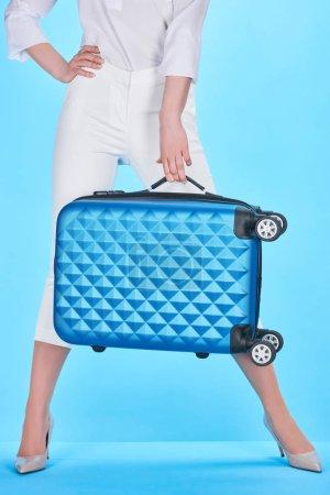 Photo pour Vue recadrée de la femme posant avec la main sur la hanche et sac de voyage bleu sur fond bleu - image libre de droit