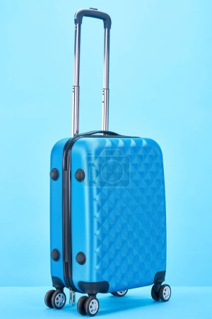 blue travel bag with handle on wheels on blue background