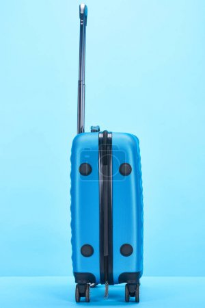 Photo for Blue colorful travel bag with handle on wheels on blue background with copy space - Royalty Free Image