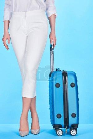 Foto de Vista recortada de la mujer que sostiene la manija de azul colorido bolso de viaje sobre fondo azul - Imagen libre de derechos