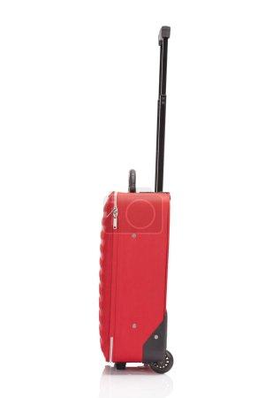 Photo pour Vue latérale de la valise colorée texturée à roues rouges avec poignée isolée sur blanc - image libre de droit
