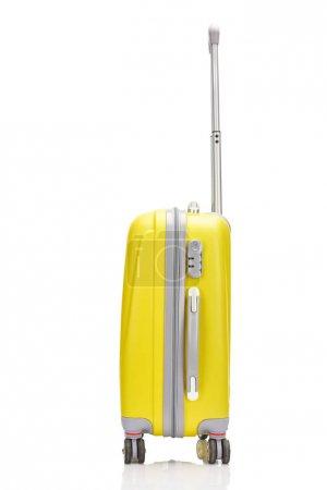 Photo pour Vue latérale de la valise colorée à roulettes en plastique jaune avec poignée isolée sur blanc - image libre de droit