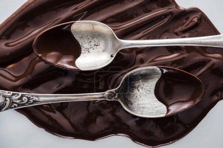 Ansicht der Löffel mit Schokolade und geschmolzener Schokolade auf weißem Hintergrund