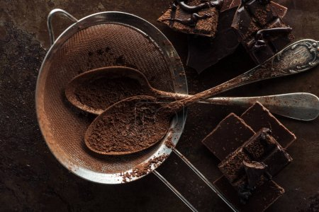 Photo for Top view of dirty strainer, vintage spoons and pieces of chocolate bar on rust metal background - Royalty Free Image