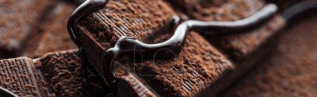 Panoramaaufnahme von Stücken dunkler Schokolade mit flüssiger Schokolade