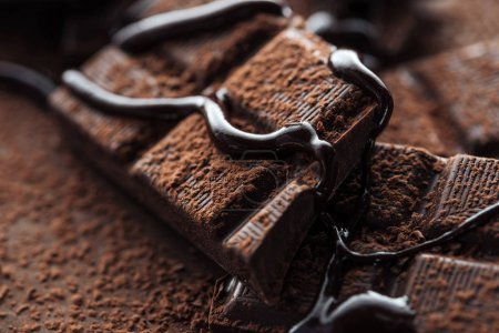 Photo for Close up view of pieces of dark chocolate bar with liquid chocolate and cocoa powder - Royalty Free Image