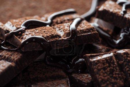 Nahaufnahme von geschmolzener Schokolade mit Stücken von dunkler Schokolade und Kakaopulver
