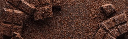 Photo for Panoramic shot of pieces of chocolate with liquid chocolate and cocoa powder on metal background - Royalty Free Image