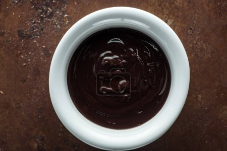 Photo for Top view of bowl with melted chocolate on rust metal background - Royalty Free Image