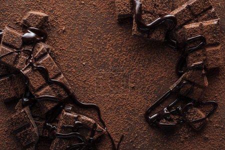 Ansicht von Schokoladenstücken mit flüssiger Schokolade und Kakaopulver auf metallischem Hintergrund