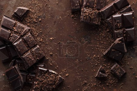 Photo for Top view of pieces of chocolate bar with chocolate chips on rust metal background - Royalty Free Image