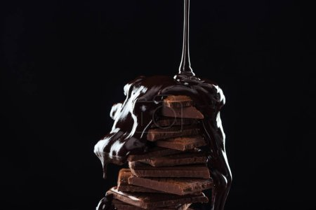 Photo for Hot melted chocolate pouring on chocolate stack, isolated on black - Royalty Free Image