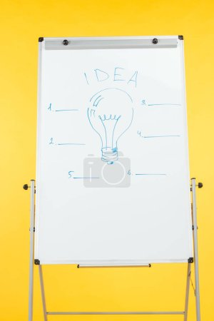 Foto de Word idea with light bulb drawn on white flipchart isolated on yellow - Imagen libre de derechos