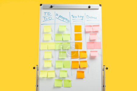 Foto de White office board with sticky notes isolated on yellow - Imagen libre de derechos