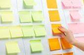 """Постер, картина, фотообои """"cropped view of businesswoman attaching sticky notes with copy space on white flipchart"""""""