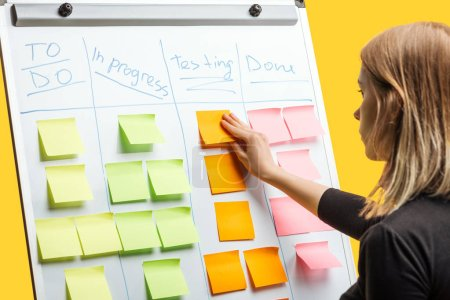 smart businesswoman standing near white flipchart, attaching sticky notes with copy space