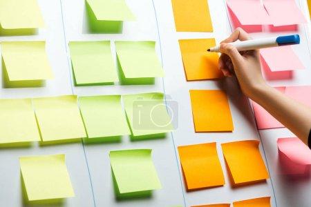 Photo pour Vue recadrée de la femme d'affaires écrivant sur des notes d'autocollants avec l'espace de copie - image libre de droit