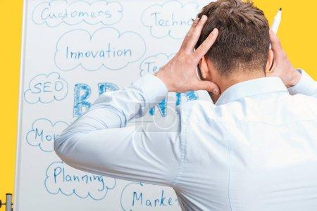 Photo pour Vue arrière de l'homme d'affaires restant près du conseil blanc de bureau avec des mots, retenant des mains sur la tête - image libre de droit