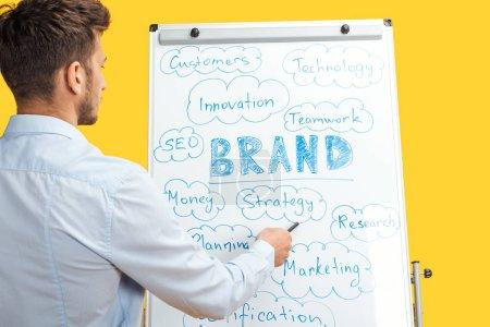 Photo pour Vue arrière de l'homme d'affaires debout près du tableau blanc de bureau, pointant vers les mots sur le tableau à feuilles mobiles - image libre de droit