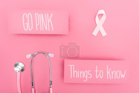 Photo for Top view of stethoscope and pink breast cancer sign near go pink and things to know lettering on pink background - Royalty Free Image