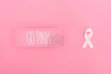 Photo for Top view of go pink lettering on card and breast cancer sign on pink background - Royalty Free Image