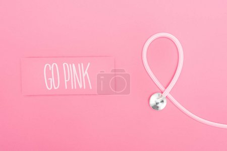 Photo for Top view of stethoscope and go pink lettering on pink background - Royalty Free Image