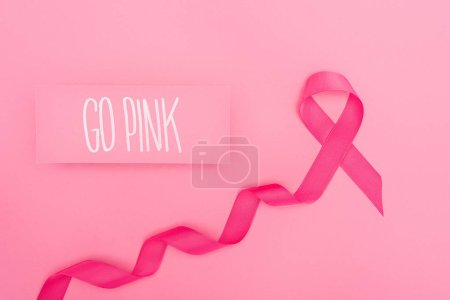 Photo for Top view of card with go pink lettering and crimson breast cancer ribbon on pink background - Royalty Free Image