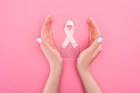 Photo for Partial view of female hands near pink breast cancer sign on pink background - Royalty Free Image