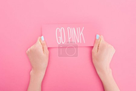 Photo for Partial view of woman holding pink card with go pink lettering on pink background - Royalty Free Image