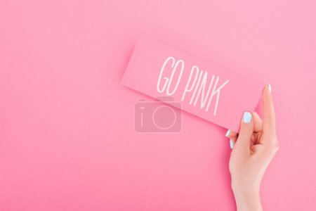 Photo for Partial view of woman holding card with go pink lettering on pink background - Royalty Free Image