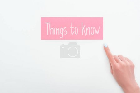 Photo for Partial view of woman pointing with finger at pink card with things to know lettering on white background - Royalty Free Image