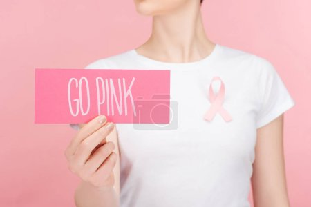 Photo for Selective focus of woman with pink breast cancer sign holding pink card with go pink lettering isolated on pink - Royalty Free Image