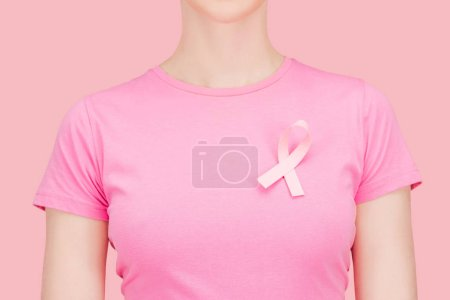 Photo pour Vue recadrée de femme en t-shirt rose avec cancer du sein en soie chantant isolé sur rose - image libre de droit