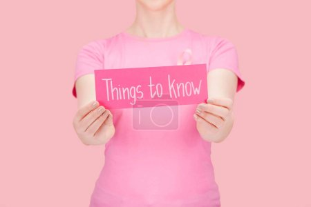 Photo for Selective focus of woman in pink t-shirt holding card with things to know lettering isolated on pink, breast cancer concept - Royalty Free Image