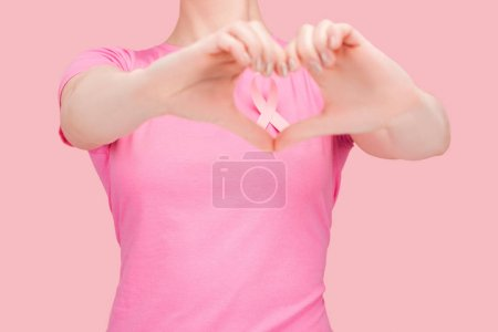 Photo for Cropped view of woman in pink t-shirt showing heart sign with hands around breast cancer ribbon isolated on pink - Royalty Free Image