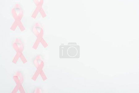 Photo pour Vue du haut des signes de cancer du sein rose soie sur fond blanc avec espace de copie - image libre de droit