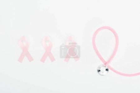 Photo pour Pose plate avec stéthoscope et signes de cancer du sein rose sur fond blanc - image libre de droit