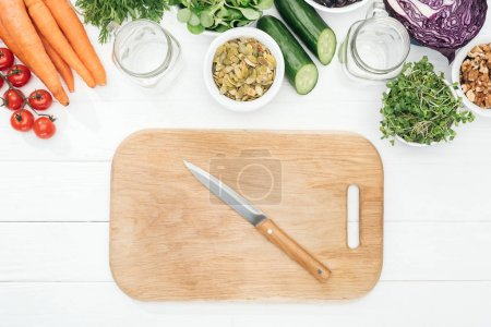 Photo for Top view of fruits and vegetables near glass jars, knife and chopping board on wooden white table with copy space - Royalty Free Image