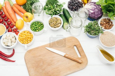 top view of fresh fruits and vegetables near glass jars on wooden white table with chopping board and knife
