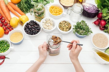 Photo pour Vue recadrée de femme ajoutant des écrous dans le pot avec la salade sur la table blanche en bois - image libre de droit