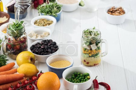 Photo for Ingredients in bowl near glass jars with salad on wooden white table - Royalty Free Image